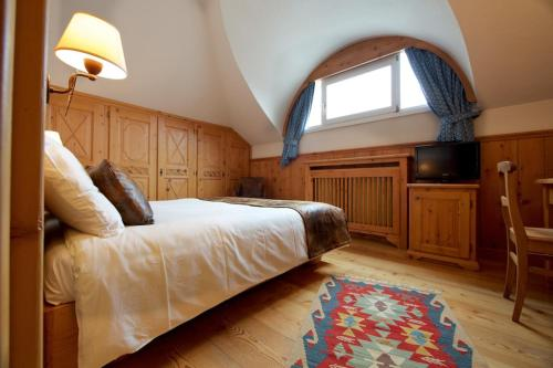 A bed or beds in a room at Hotel Bouton d'Or - Courmayeur