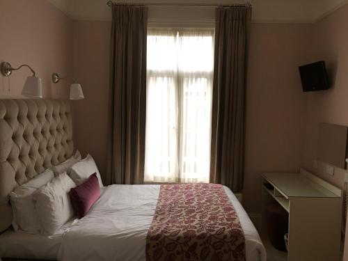 A bed or beds in a room at Maples House Hotel