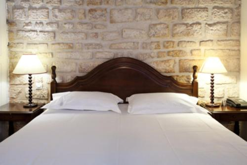 A bed or beds in a room at Tonic Hôtel du Louvre