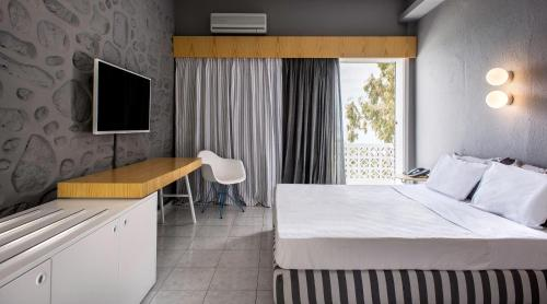 A bed or beds in a room at Alkistis Beach Hotel
