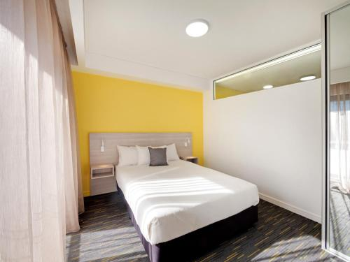 A bed or beds in a room at Value Suites Penrith