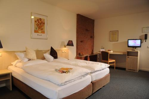 A bed or beds in a room at Air Hotel Wartburg