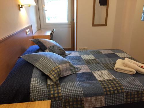 A bed or beds in a room at Hostal Rio De Castro