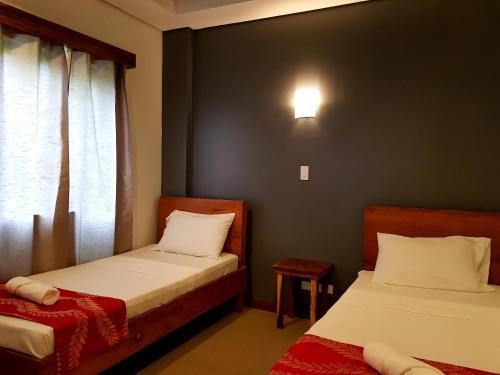 Un pat sau paturi într-o cameră la Acacia Garden Inn