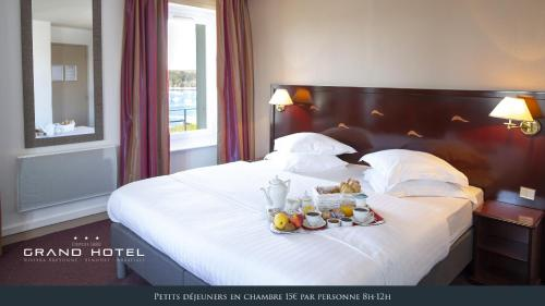 A bed or beds in a room at Grand Hôtel Bénodet Abbatiale Riviera Bretonne