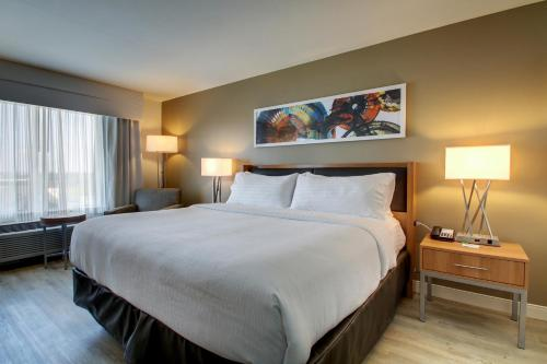 A bed or beds in a room at Holiday Inn & Suites Peoria at Grand Prairie