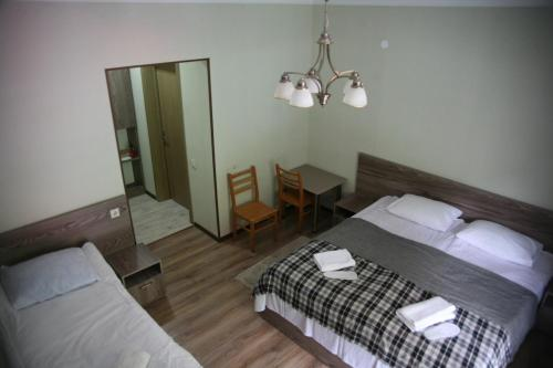 A bed or beds in a room at Garden Hotel Pasanauri