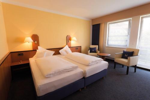 A bed or beds in a room at Hotel Markkleeberger Hof