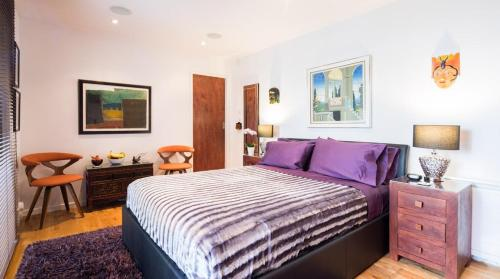 A bed or beds in a room at Romantic Bungalow in Notting Hill