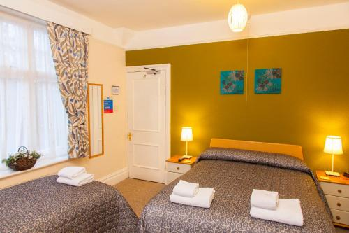A bed or beds in a room at Gatwick Turret Guest House