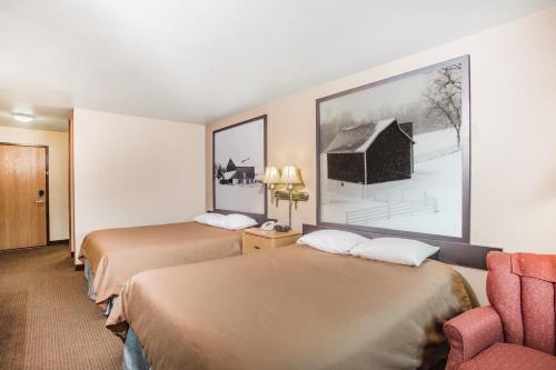A bed or beds in a room at Super 8 by Wyndham Monroe WI