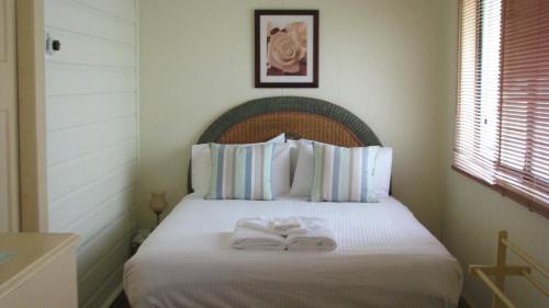 A bed or beds in a room at Rose Cottage Hunter Valley