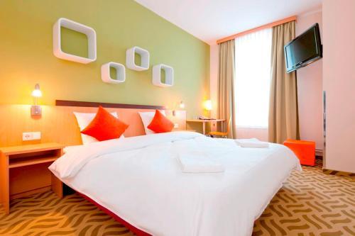 Ein Bett oder Betten in einem Zimmer der Unterkunft ibis Styles Berlin City Ost