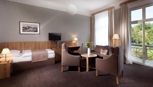 A bed or beds in a room at Spa & Kur Hotel Praha