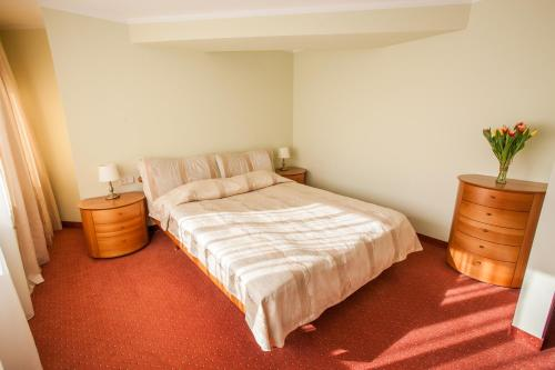 A bed or beds in a room at AirInn Vilnius Hotel