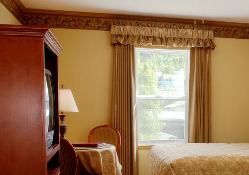 A bed or beds in a room at Westmark Inn Dawson City