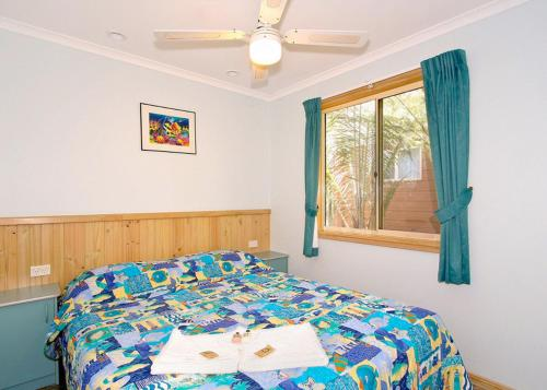 A bed or beds in a room at Lorikeet Holiday Park
