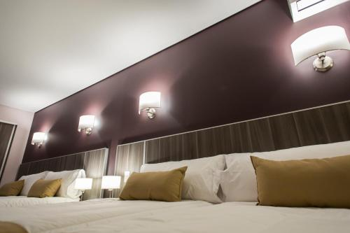 A bed or beds in a room at Mérit Iguazú Hotel