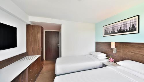 A bed or beds in a room at Fairfield by Marriott Chennai OMR
