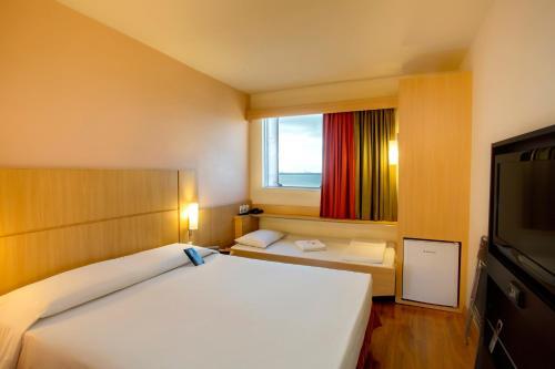 A bed or beds in a room at Ibis Vitoria Praia de Camburi