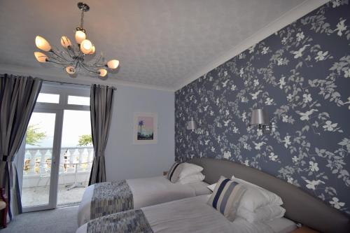 A bed or beds in a room at The Babbacombe Hotel