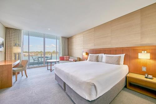 A bed or beds in a room at The Sebel Mandurah