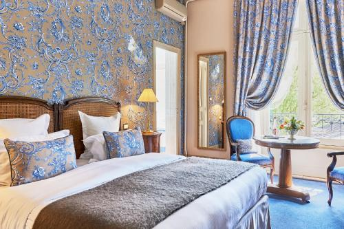 A bed or beds in a room at Le Clos - Relais & Chateaux