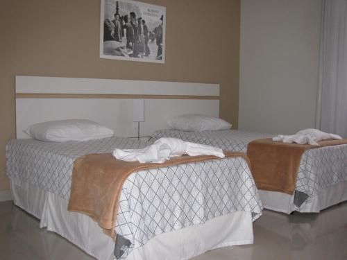 A bed or beds in a room at Monza Comfort Hotel
