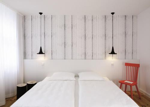 A bed or beds in a room at Hotel AMANO Rooms & Apartments