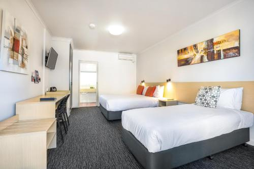 A bed or beds in a room at Nightcap at Ferntree Gully Hotel Motel