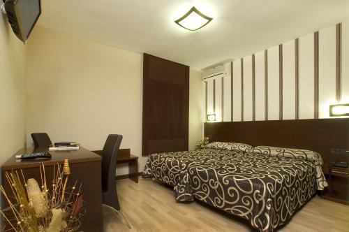 A bed or beds in a room at Hotel Ciudad de Plasencia