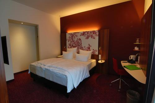 A bed or beds in a room at IBB Hotel Ingelheim
