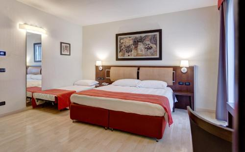A bed or beds in a room at Stadio Hotel