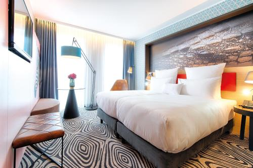 A bed or beds in a room at NYX Hotel Munich by Leonardo Hotels