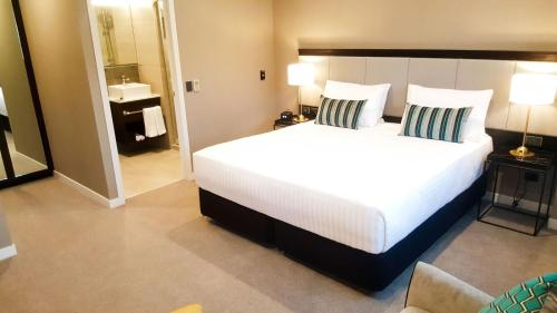A bed or beds in a room at The Sebel Auckland Manukau