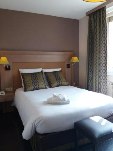 """A bed or beds in a room at AUBERGE de """"L'Hostellerie le Saint Laurent"""" - Hotel Restaurant - Institut de """"Bien etre"""" et ses """"Appart Hotel"""""""