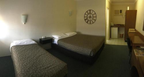 A bed or beds in a room at Casino Motor Inn