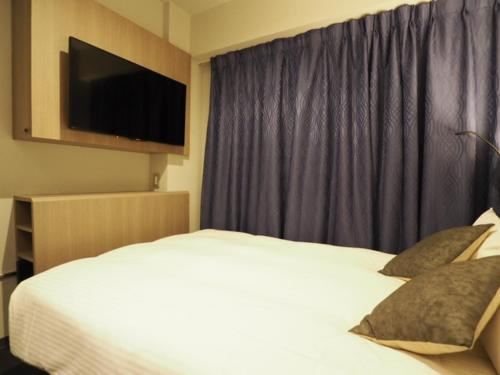 A bed or beds in a room at Haneda Inn