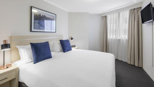 A bed or beds in a room at Oaks Sydney Castlereagh Suites
