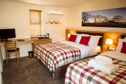 A bed or beds in a room at The Fir Tree Country Hotel