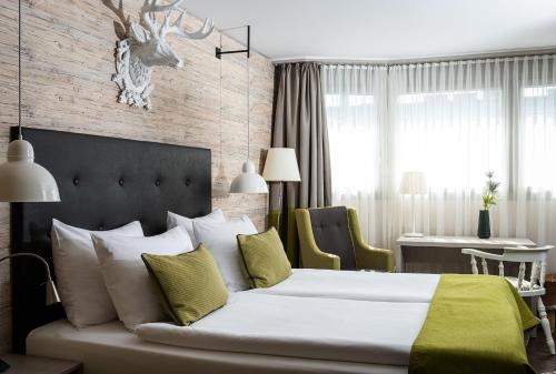 A bed or beds in a room at AMERON Luzern Hotel Flora