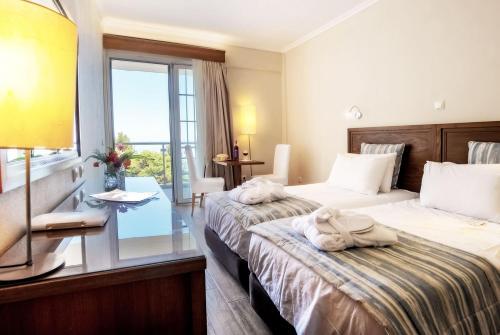 Кровать или кровати в номере Alexander the Great Beach Hotel