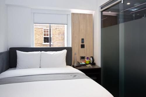 A bed or beds in a room at Z Hotel Tottenham Court Road