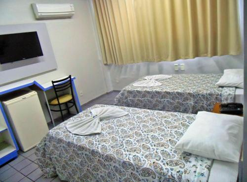 A bed or beds in a room at Titão Plaza Hotel