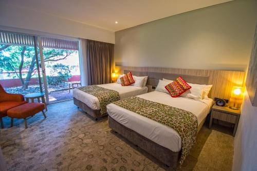 A bed or beds in a room at Desert Gardens Hotel