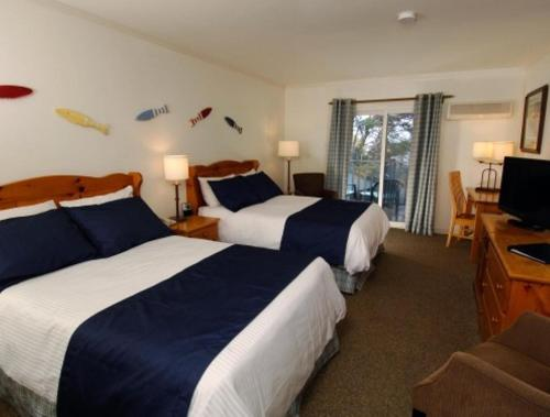A bed or beds in a room at White Point Beach Resort