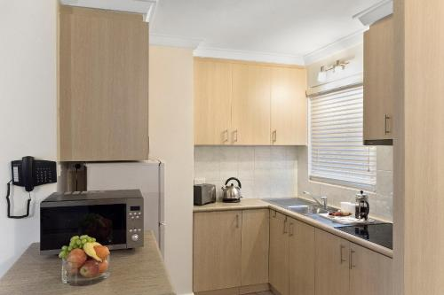 A kitchen or kitchenette at The Peninsula Riverside Serviced Apartments