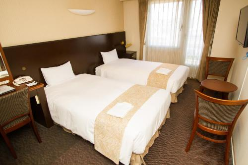 A bed or beds in a room at Hotel Camelot Japan