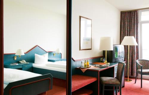 A bed or beds in a room at Tryp by Wyndham Bad Bramstedt
