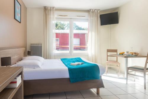 A bed or beds in a room at Zenitude Hôtel-Résidences Nantes - La Beaujoire